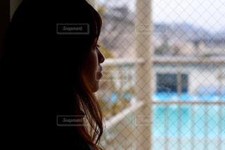 フェンスの前に立っている女性の写真・画像素材[995253]