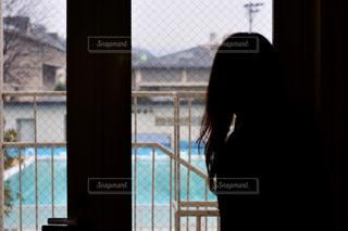 ウィンドウの前に立っている人の写真・画像素材[995257]