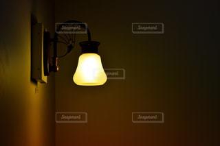 暗い部屋に座っているランプの写真・画像素材[1009461]