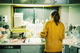 キッチンで立っている女性の写真・画像素材[1009467]