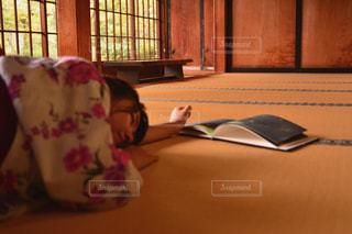 窓の前のテーブルに座っている人の写真・画像素材[1009470]