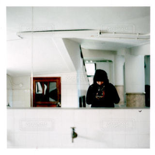 鏡の前に立っている男の写真・画像素材[1009492]