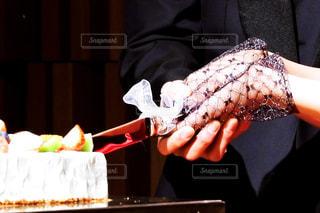 テーブルの上のケーキを持っている手 - No.1009506