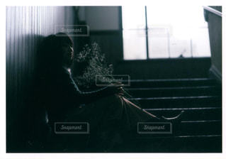 暗い部屋に座っている人の写真・画像素材[1022136]