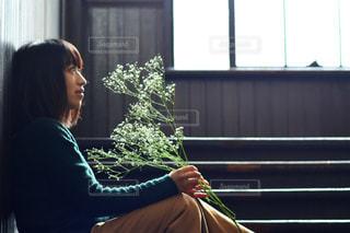 窓の前でベンチに座っている女性の写真・画像素材[1022144]