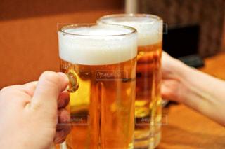 テーブルにビールのグラスを持っている手の写真・画像素材[1022167]
