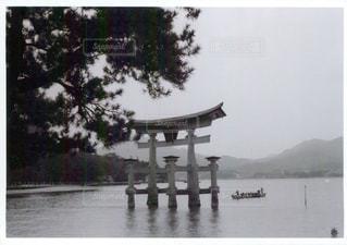水の体の横に立っている人のグループの写真・画像素材[1022522]