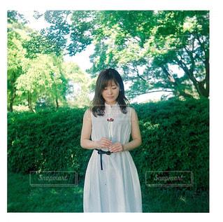 森の前に緑のドレスの立っている人の写真・画像素材[1160126]