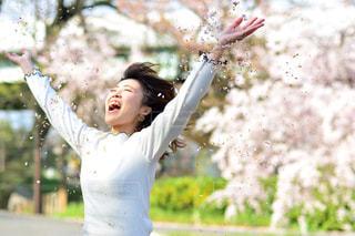女性,春,桜,屋外,京都,緑,晴れ,手,花びら,楽しい,樹木,人物,笑顔,微笑み,伏見