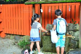 フェンスの前に立っている少年の写真・画像素材[1181563]