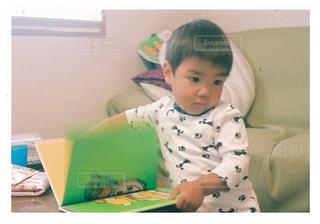 ベッドの上に座っている若い男の子の写真・画像素材[1181617]