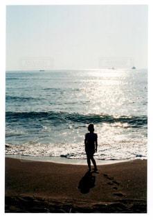海の横にあるビーチの上を歩く男 - No.1228243