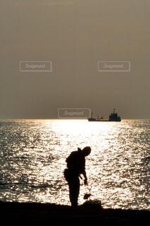水の体の横に立っている人の写真・画像素材[1228262]
