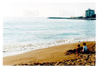 水の体の近くのビーチに座っている人の写真・画像素材[1228264]