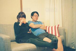 男とソファの上に座っている女性の写真・画像素材[1228956]