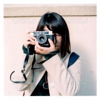 カメラにポーズ鏡の前に立っている人の写真・画像素材[1243737]