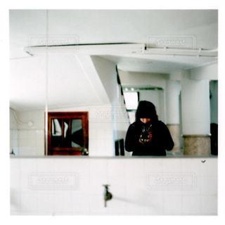 鏡の前に立っている男の写真・画像素材[1243738]