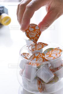 オレンジ ジュースのグラスを持っている手の写真・画像素材[1259826]