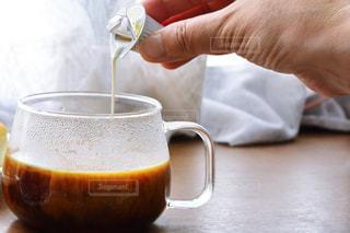 近くに一杯のコーヒーを保持している人のの写真・画像素材[1259848]