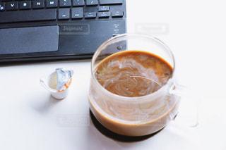 一杯のコーヒーをキーボードの隣に座っての写真・画像素材[1260533]