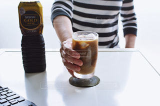 一杯のコーヒーをテーブルに着席した人の写真・画像素材[1260553]
