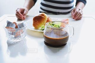 食品のプレートをテーブルに座っている女性 - No.1260563