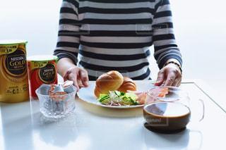 食品のプレートをテーブルに座っている女性の写真・画像素材[1260567]