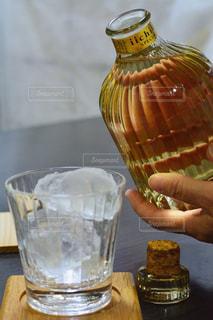 テーブルの上のビールのガラスを保持している人の写真・画像素材[1267299]