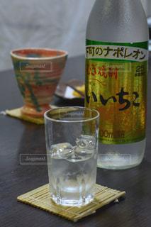 テーブルの上のコーヒー カップの横にガラスの瓶の写真・画像素材[1267306]