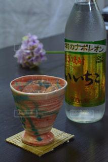 テーブルの上のコーヒー カップの横にガラスの瓶の写真・画像素材[1267308]