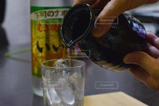 テーブルにビールのグラスを持っている手の写真・画像素材[1267326]
