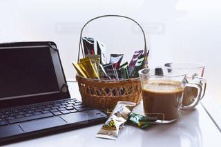 一杯のコーヒーとテーブルの上に座っているラップトップ コンピューターの写真・画像素材[1307241]