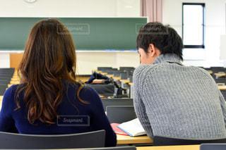 コンピューターの前で机に座っている女性の写真・画像素材[1307467]