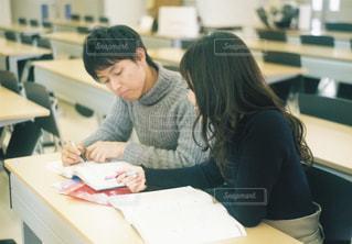 ラップトップを使用してテーブルに座っている女性の写真・画像素材[1307501]