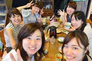 カメラにポーズのテーブルに座っている人々 のグループの写真・画像素材[1357614]