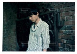 レンガ壁の前に立っている男の写真・画像素材[1360219]
