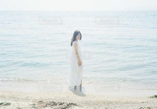 水の体の近くのビーチに立っている人の写真・画像素材[1403264]