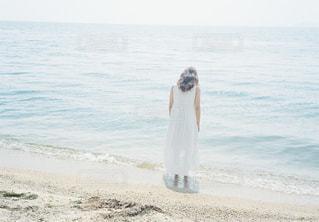水の体の近くのビーチに立っている人の写真・画像素材[1403265]