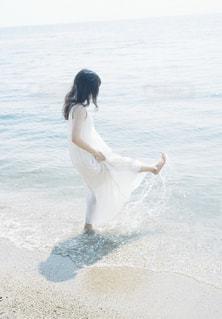 水の体の横に立っている人の写真・画像素材[1403266]