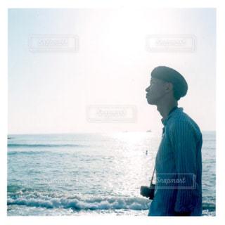 水の体の横に立っている人の写真・画像素材[1403796]