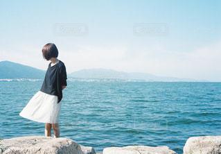 水の体の横に立っている人の写真・画像素材[1406904]