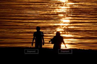 バック グラウンドで夕日を持つ人の写真・画像素材[1407062]