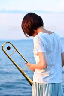水の体の横に立っている少年の写真・画像素材[1407166]