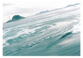 山の上に波に乗っている男の写真・画像素材[1407517]