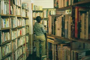 書店の棚の横に立っている人の写真・画像素材[1562529]