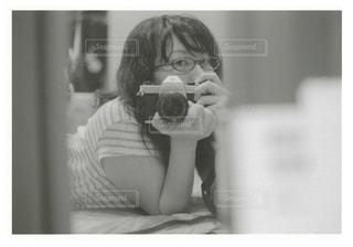 カメラにポーズを鏡の前で彼女の歯を磨く女性の写真・画像素材[1646548]