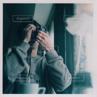 鏡の前で携帯電話で話す人の写真・画像素材[1842919]