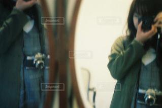 カメラにポーズ鏡の前に立っている女性の写真・画像素材[1852770]
