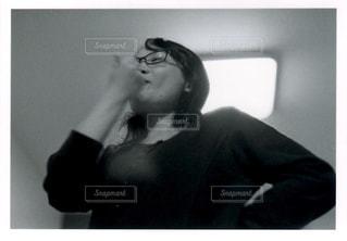 鏡の前に立つ人がカメラに向かってポーズをとるの写真・画像素材[2497018]