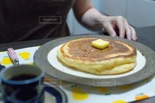 食べ物の皿を持ってテーブルに座っている人の写真・画像素材[2508349]